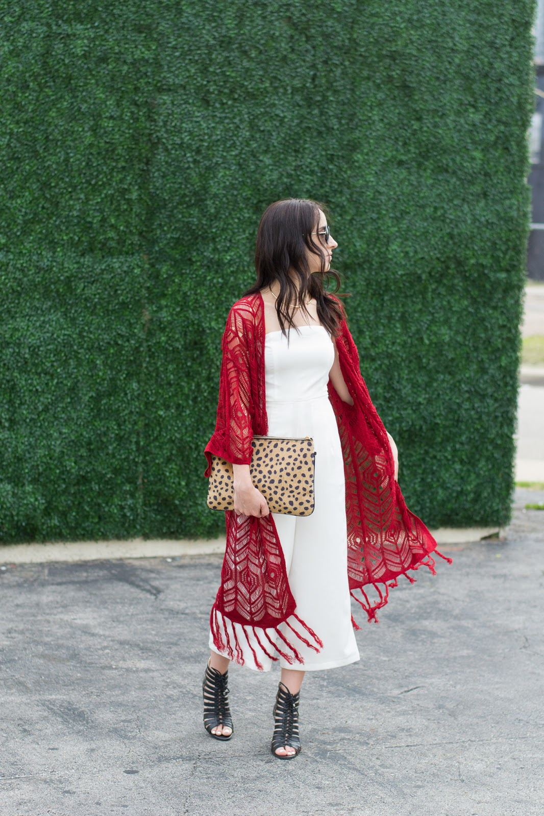 Mixing styles with boho cardigan, chic white jumpsuit, gold accessories and leopard clutch