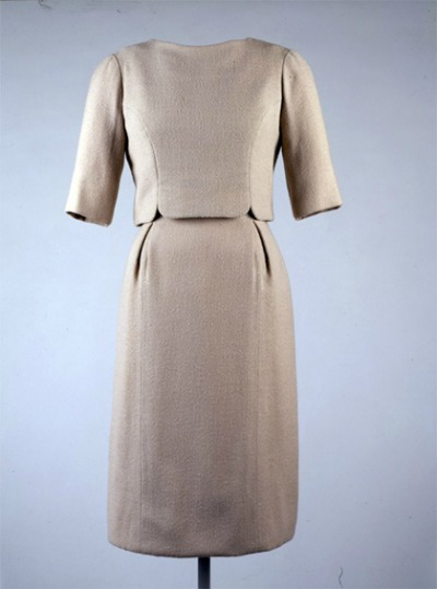 Beige wool crep dress with short overblouse displayed on mannequin. Mrs Kennedy wore this Oleg Cassini design to inaugural ceremonies