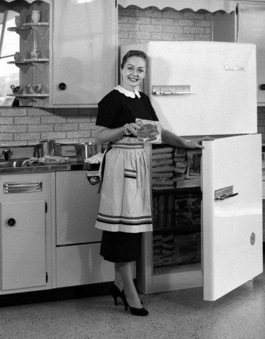 1950s smiling woman housewife in kitchen taking frozen food out of refrigerator. Oh Wait and other stories of the Refrigerator. marchmatron.com