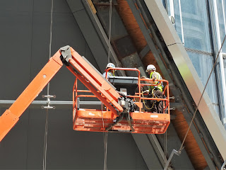 Workers in a long-arm cherry picker crane basket