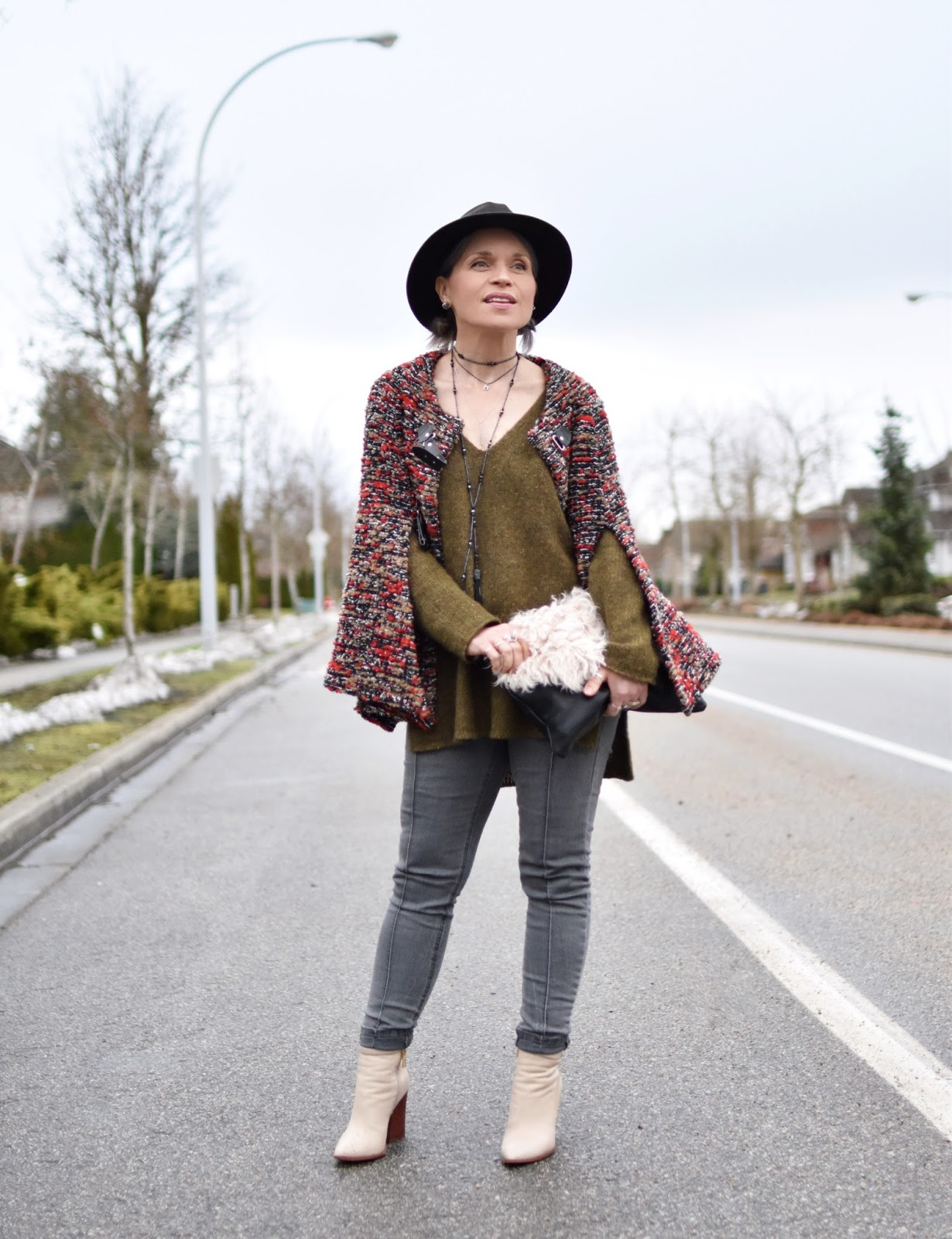 Monika Faulkner outfit inspiration - styling a tunic sweater with a cape, skinny jeans, ivory booties, and a fedora