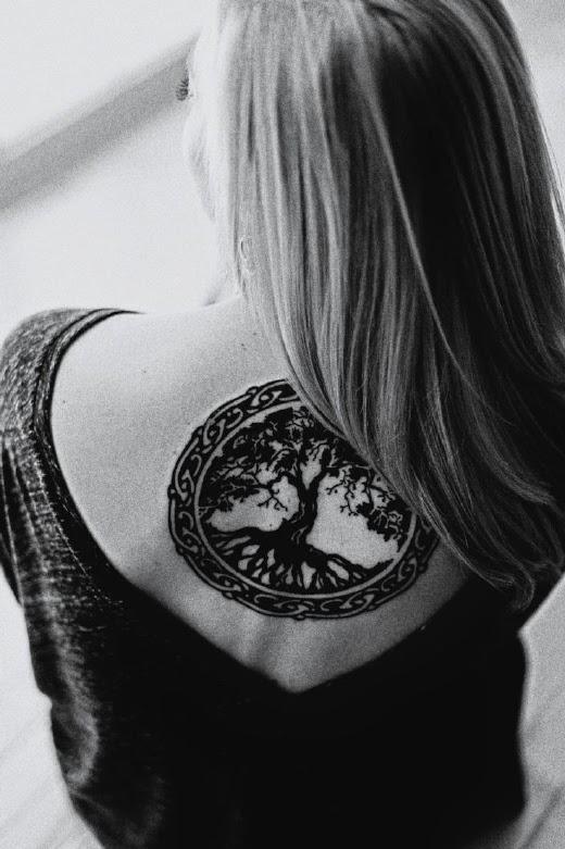 vemos a una chica que luce un tatuaje de arbol