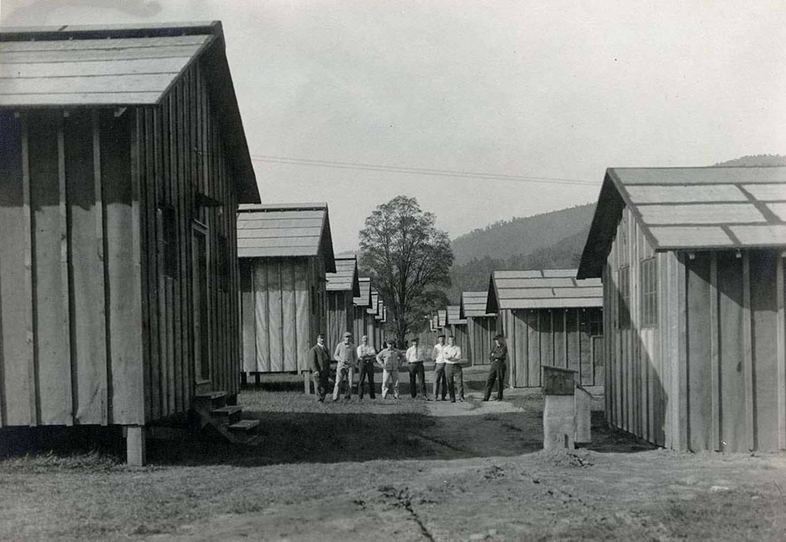 Internees pose among the barracks they helped to construct.