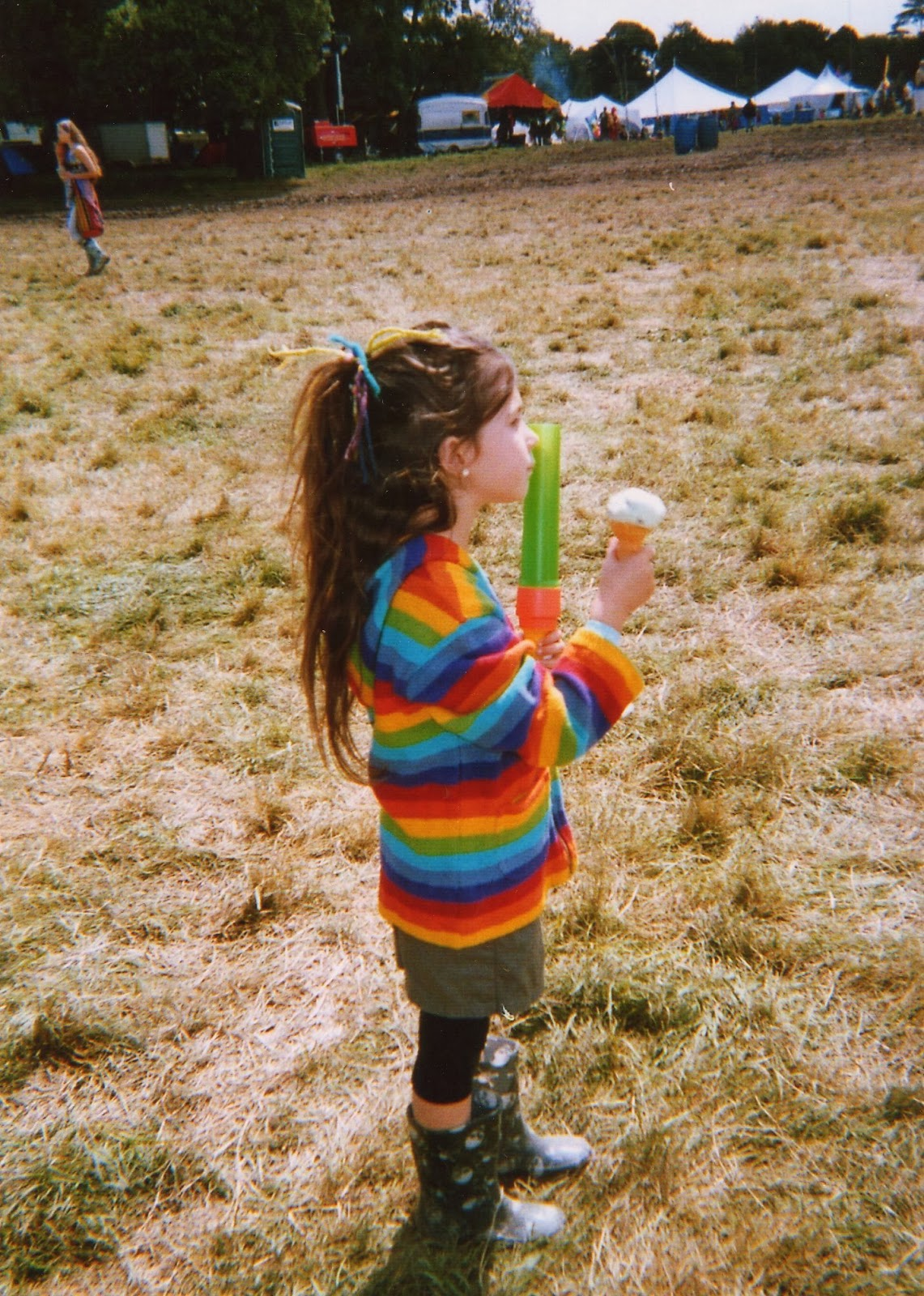 hippy child in wellies at a festival eating icecream