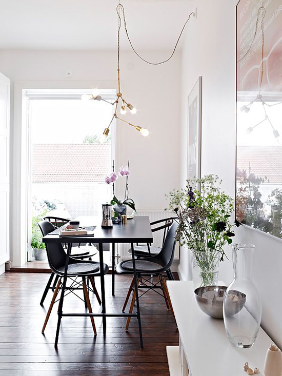 Modern brass chandelier in the dining room. Image via Stadshem.