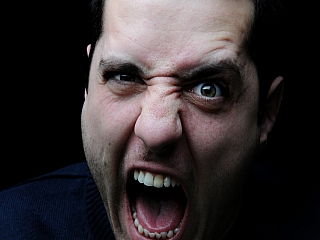 A man who is having anger problems makes an angry face
