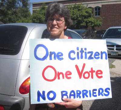 Woman holding hand-painted sign reading One Citizen One Vote No Barriers