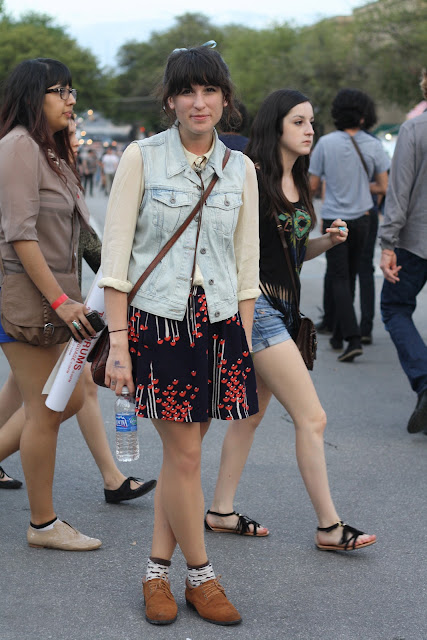 girl wearing a white shirt, denim vest, and printed skirt at sxsw