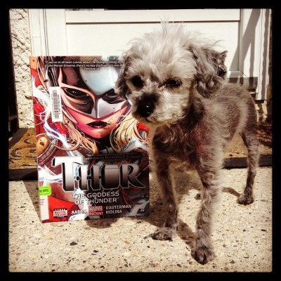 Murchie stands outdoors on a concrete step. Slightly behind and to one side of him is a hardcover copy of Thor Volume One: Goddess of Thunder. Its cover features a close-in illustration pale-skinned blonde woman wearing a chrome mask that covers the top half of her face. Lightning crackles around her.