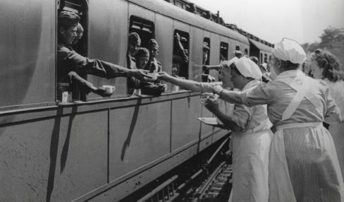 Wounded and invalids. German wounded return their empty coffee cups to Red Cross nurses just prior to departure. Location unknown. 1941. From the collection of the Nationaal Archief of the Netherlands.