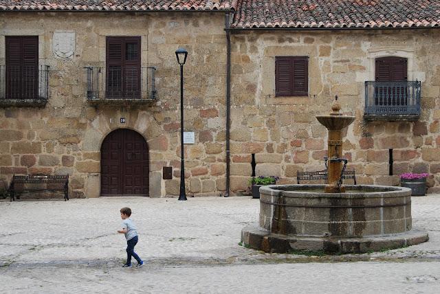 Niño en la plaza de San Martín de Trevejo con sus fachadas de piedra y su fuente circular en el centro