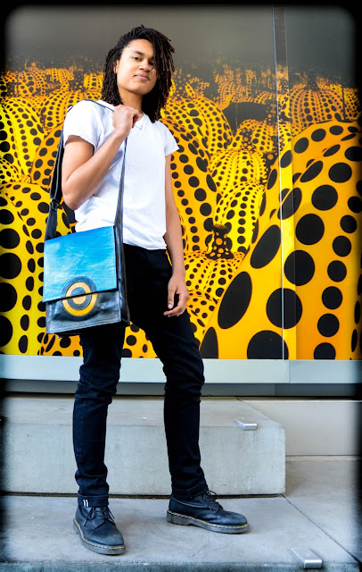 Maya with the blue, yellow, and black leather Chemical Wedding shoulder handbag with adjustable strap.