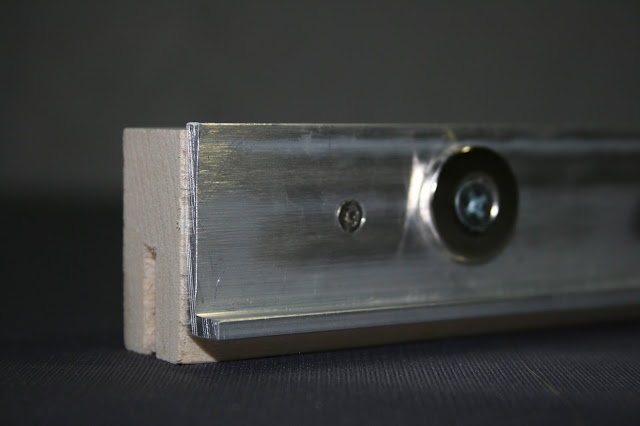 closeup of magnetic mounting slat bracket for rare earth magnet mounting system to safely display and mount textiles and artifacts for exhibit. Gwen Spicer is a conservator in private practice who is an expert in the use of magnets for mounting artifacts and in conservation treatments.