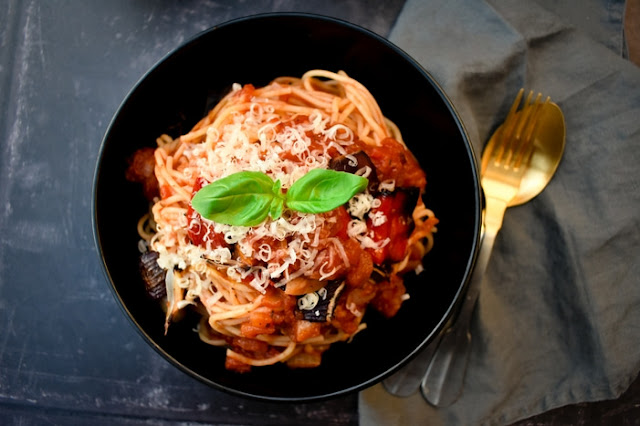 A black bowl full of spaghetti coated in tomato and roasted red pepper pasta sauce