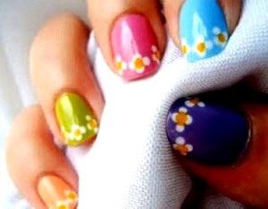 Foto de uñas pintadas de distintos colores con diseños de flores