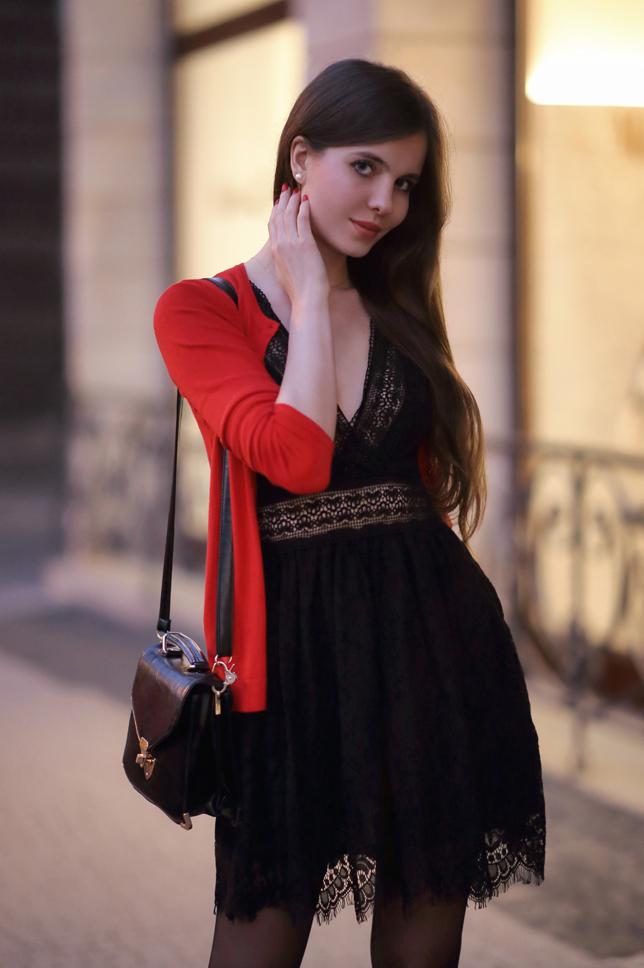 Czarna koronkowa sukienka, czerwony cardigan, czarne rajstopy i lakierowane szpilki