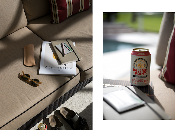poolside flatlay in orlando with ballast point ipa, contrarian magazine, moscot glasses and birkenstock sandals