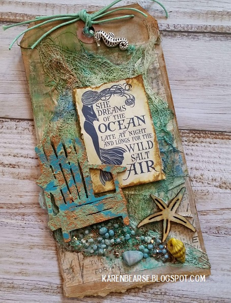 tag with an altered adirondack chair in blue/green patina. Shells and beads in blues and greens.