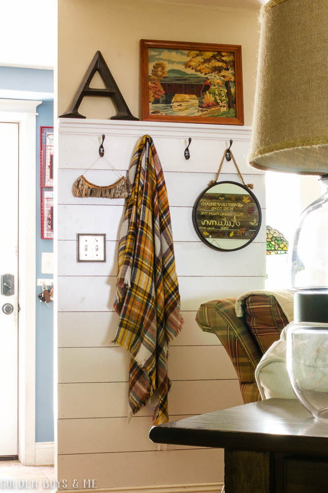 DIY planked wall with shelf and hooks in family room with plaid scarf as fall decor - www.goldenboysandme.com