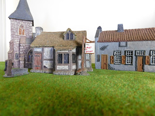 A model village with a pub, a house and a church