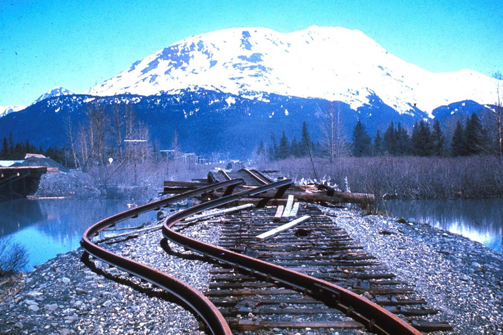 The rails in this approach to a railroad bridge near the head of Turnagain Arm, southeast of Anchorage, were torn from their ties and buckled laterally by movement of the riverbanks during a massive earthquake on March 27, 1964. The bridge was also compressed and developed a hump from vertical buckling.