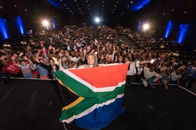 Raven Symone holding South African flag with theatre full of fans in background