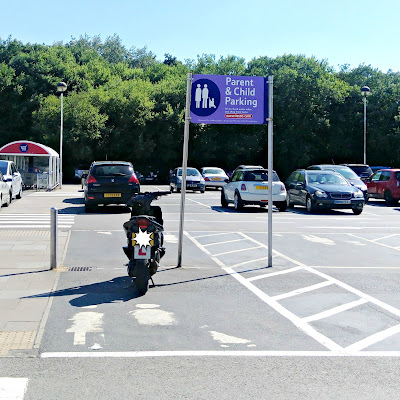 A motorbike parked in a Parent and Child space, in front of a large sign, indicating the purpose of the space.