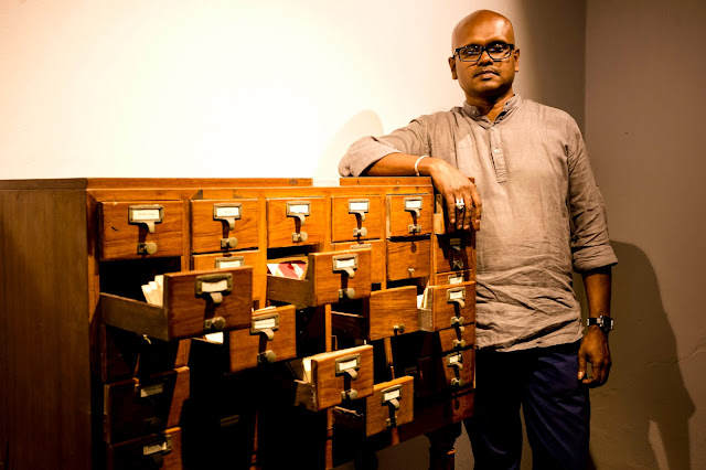 T Shanaathanan:- Artist T Shanaathanan with his installation 'Cabinet of Resisitance - 2 at KMB 2016 in  Anand Warehouse,Mattancherry.