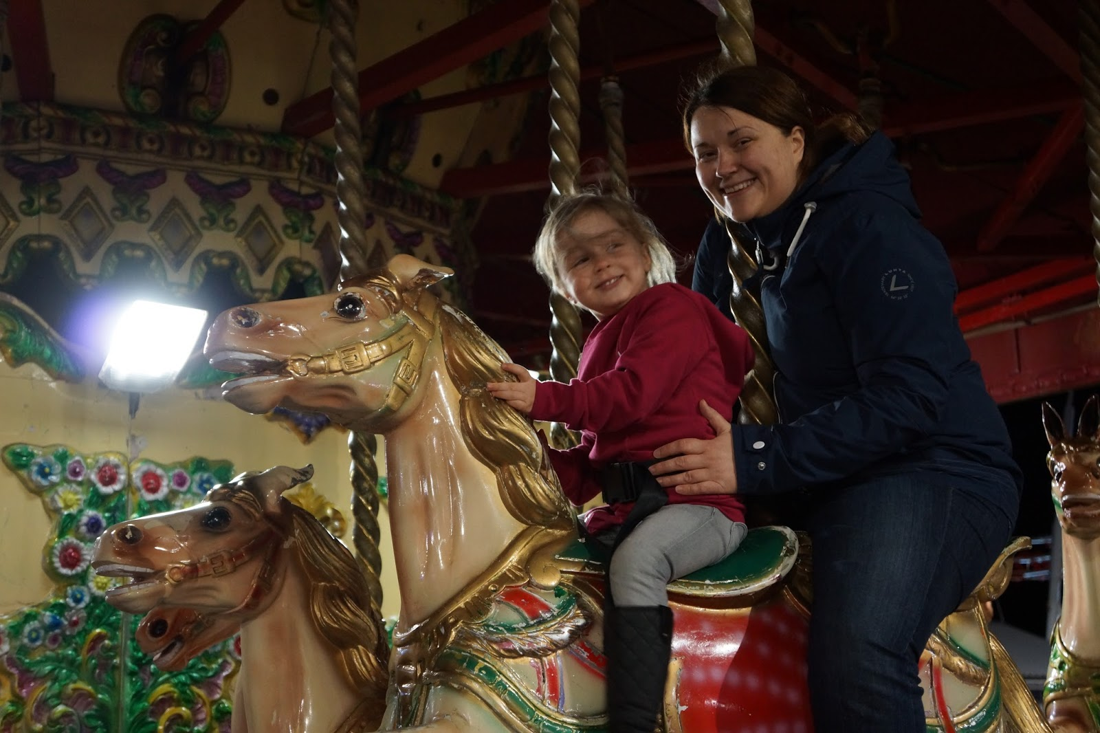 mum and daughter on a merry go around at dar at butlins minehead
