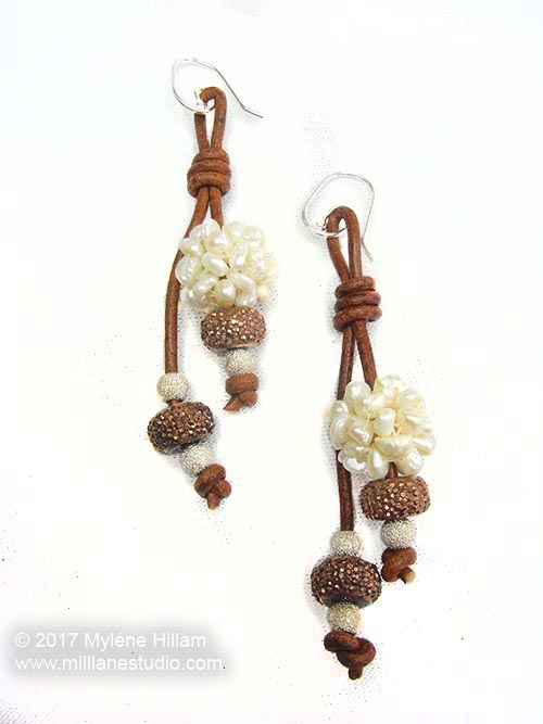 Pearl clusters, pave beads and gold dust beads strung on lengths of brown leather cord to make dangling earrings