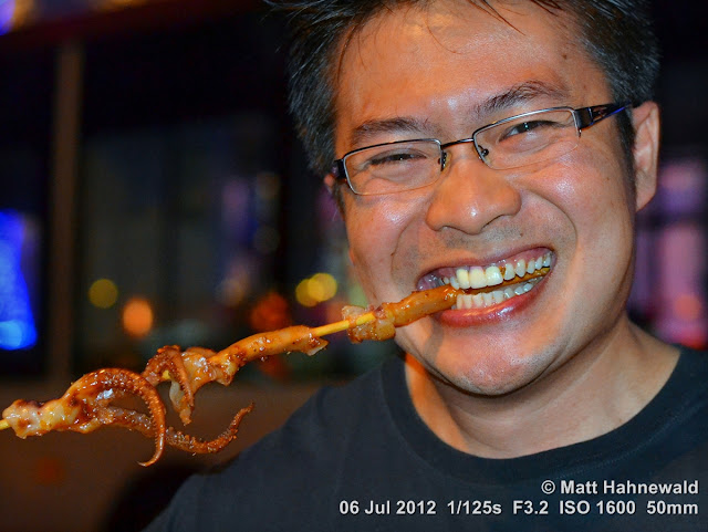 China, Beijing, Donghuamen night market, Chinese food delicacies, unusual food, bizarre Chinese foods, exotic food, Chinese man eating bizarre food, portrait, Chinese man eating fried squid