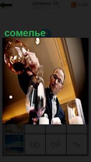 сомелье мужчина наливает вино в бокал