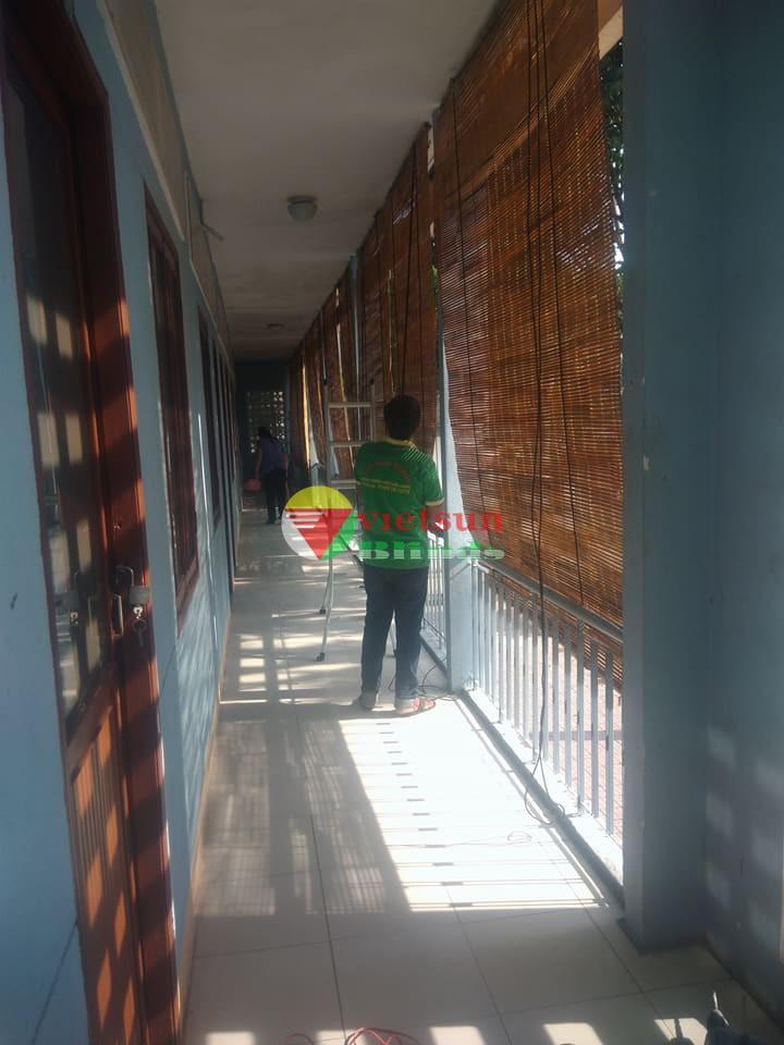 Nhân viên kỹ thuật của Việt Sun đang lắp đặt rèm tre chống nắng ngoài trời cho khách hàng.