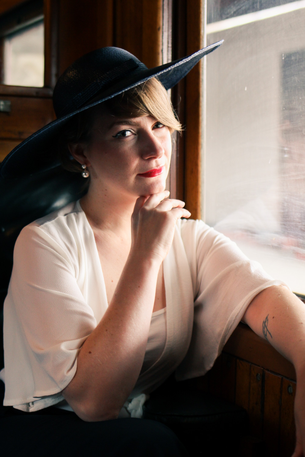@findingfemme wears navy flares and white loose sleeve blouse with navy broad brimmed vintage hat in Dior 'new look' inspired outfit on the steam train.
