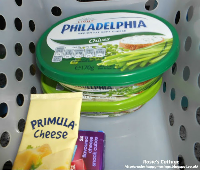 "Refrigerator organization using bins - assorted cheeses in the ""use me first"" bin."