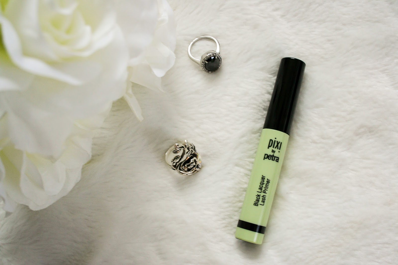 Image contains tube of lash primer, on white background, with roses and 2 rings