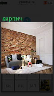 В комнате сделана стена из кирпича и стоит диван рядом