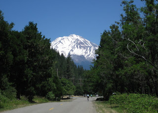 View of Mt. Shasta with cyclists heading toward the distant mountain, near Dunsmuir, California
