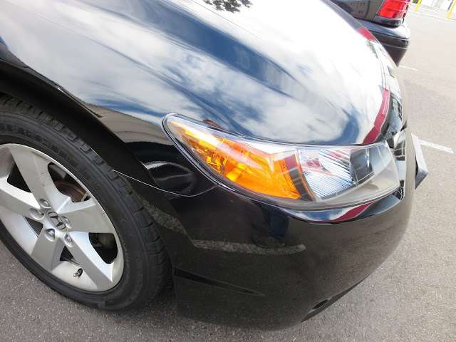 Honda Civic with damaged front bumper and fender after auto body repairs.