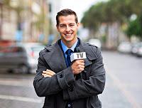 Elinde üzerinde TV yazan bir mikrofon tutarken kameraya gülümseyen erkek bir muhabir