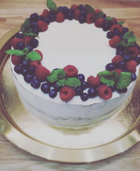 Ovocny dort zatren bilym kremem a ozdoben boruvkami, malinami a matou