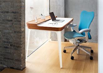 Bir cam kenarındaki beyaz uzun ayaklı küçük modern masa ve tekerlekli mavi sandalyesi