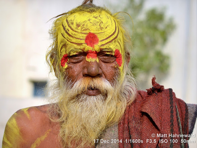 Orchha; white beard; Madhya Pradesh; old man; Indian man; sadhu; holy man; sandalwood paste; yellow tilaka; Matt Hahnewald Photography; Facing the World; photography; photo; image; Nikon D3100; Nikkor AF-S 50mm f/1.8G; prime lens; 50 mm; 4 : 3 aspect ratio; horizontal format; closeup; portrait; portraiture; street portrait; headshot; en face; front view; outdoor; colour; colourful; world cultures; cultural; character; personality; real people; human; human head; human face; eyes; mouth; facial expression; consent; empathy; rapport; encounter; emotion; environmental portrait; ethnic portrait; travel; travel portrait; travel destination; India; Pradesh; tradition; one person; male; ethnic; eye contact; posing; exotic; colour yellow; depth of field; religion; Hinduism; painted face; painted forehead; incredible