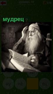 мудрец за столом с бородой читает книгу и думает
