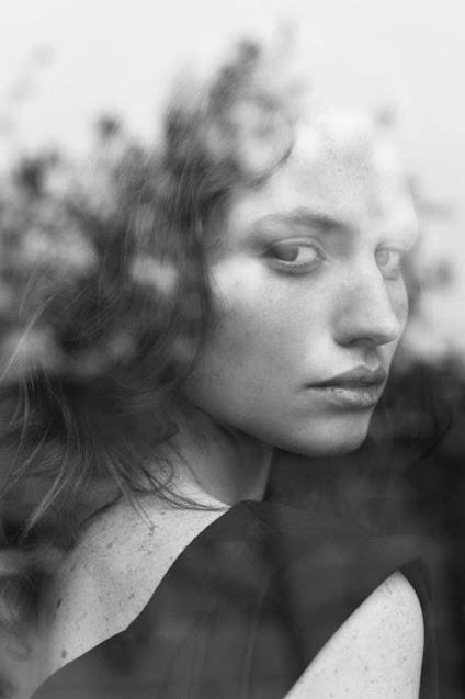 Retrato em preto e branco de uma mulher olhando sobre os ombros, fotografias com reflexos de um vidro