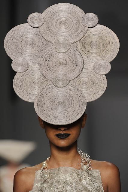 rolled newspaper hat made of circular shapes on model's head