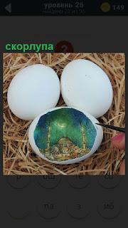 Три яйца со скорлупой, одно из которых украшено рисунком