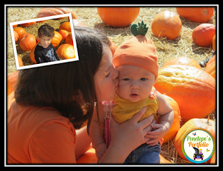An older girl holding a baby girl and kissing her on the cheek, who is wearing a cute pumpkin hat, with pumpkins in the background