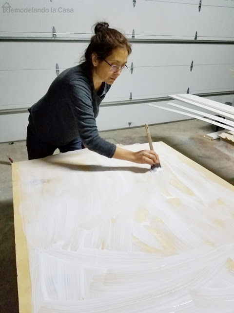 Cristina Garay applying ModPodge to plywood for a farmhouse wall art