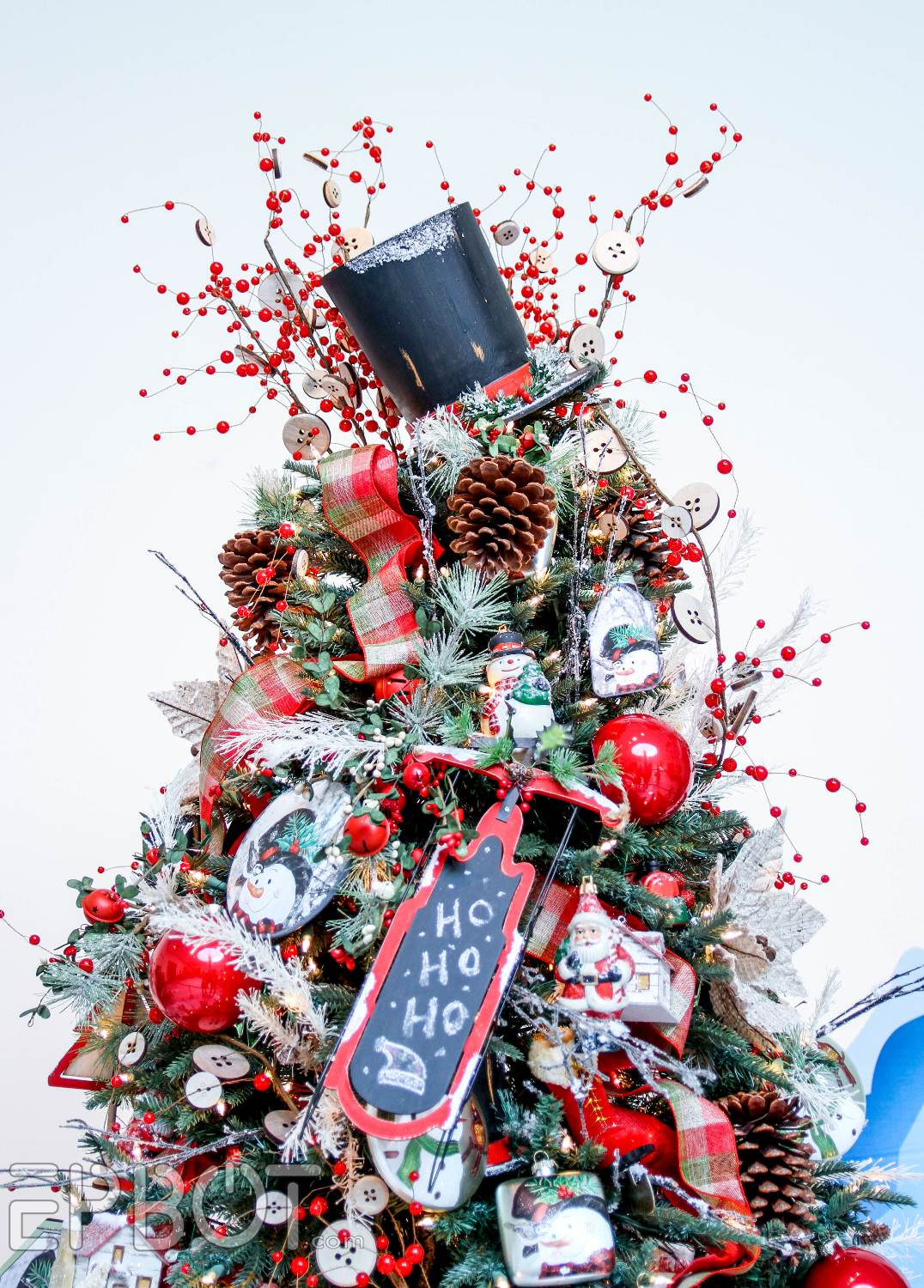im always most interested in tree toppers and this year top hats were pretty popular i like the extra berry sprigs around this one keeps it from looking